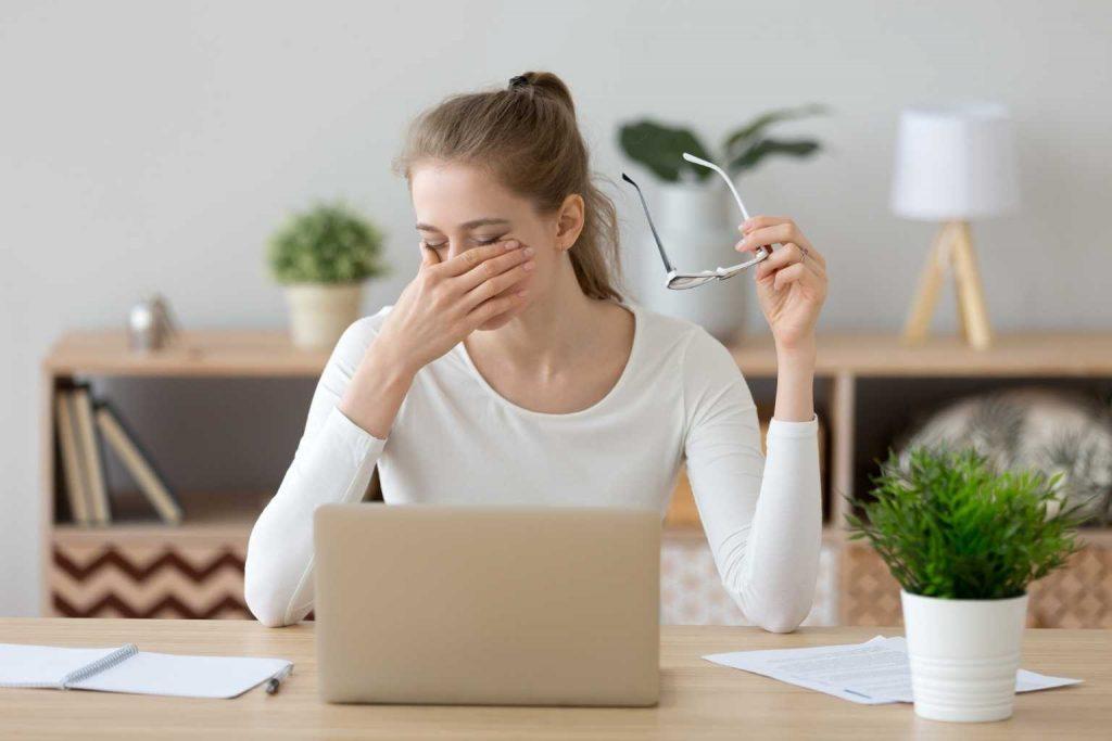Frau mit müden Augen vor Laptop