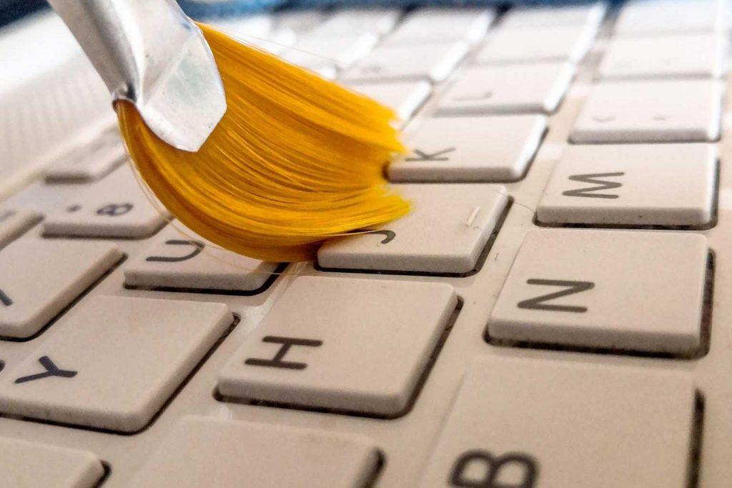 Ein Pinsel reinigt eine Tastatur.