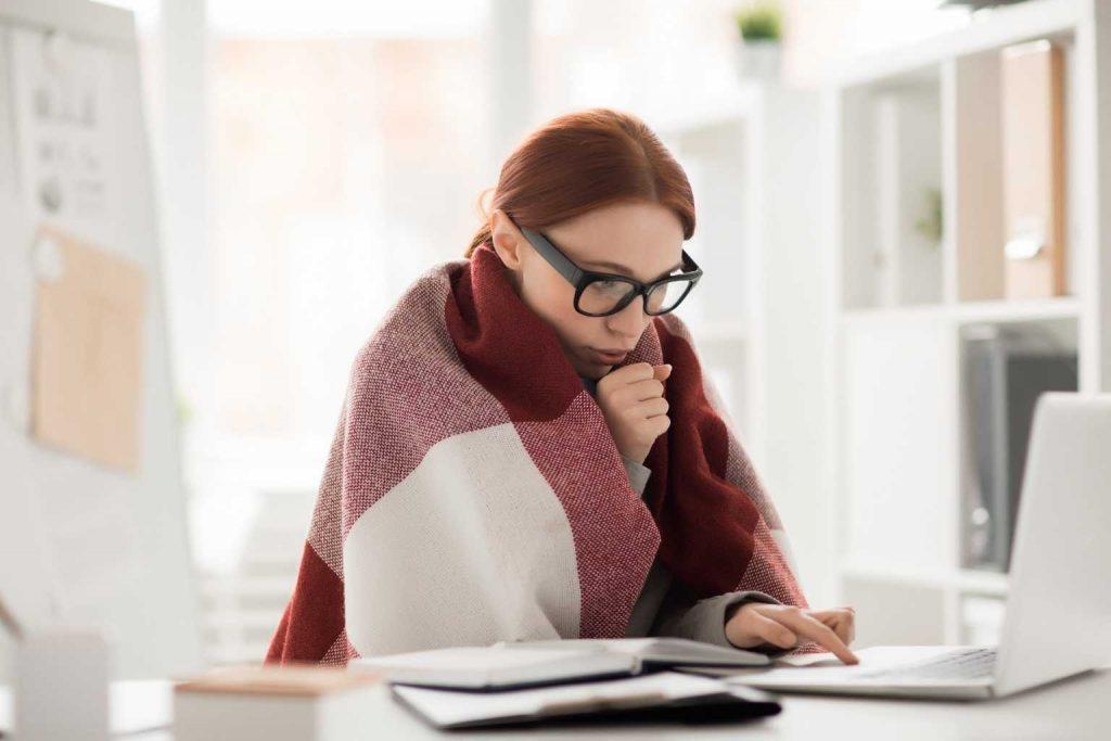 Frau in Decke am kalten Arbeitsplatz