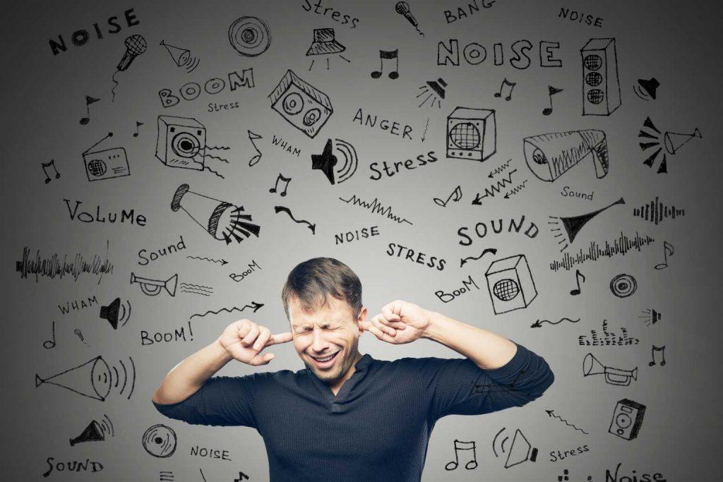 Mann mit Fingern in den Ohren um Lärm am Arbeitsplatz zu zeigen