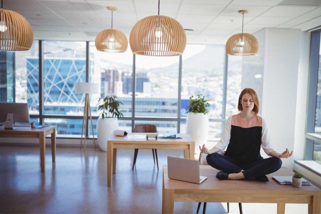 Frau meditiert auf Schreibtisch