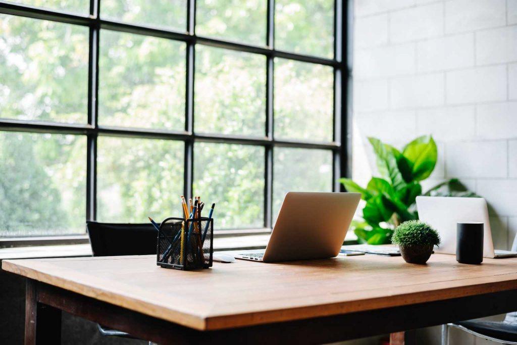 aufgeräumter Schreibtisch vor Fensterfront