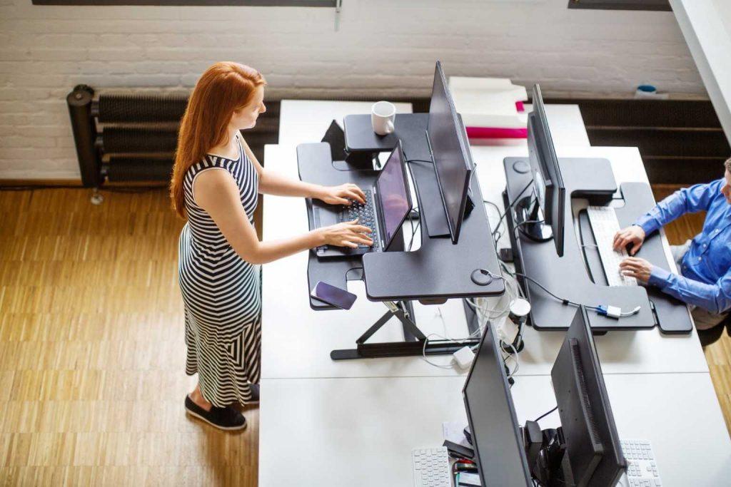 Frau an höhenverstellbarem Schreibtisch