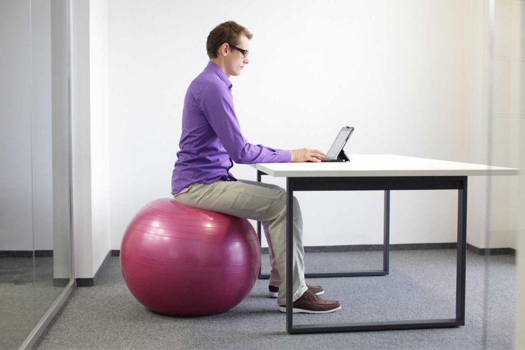 Mann auf Gymnastikball am Schreibtisch